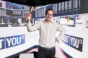 Marcel Esser with a stock exchange bell in his hand in front of an LED wall at the ABOUT YOU IPO.
