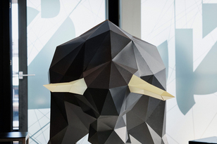 Black cardboard animal with golden horns as decorative element on white base