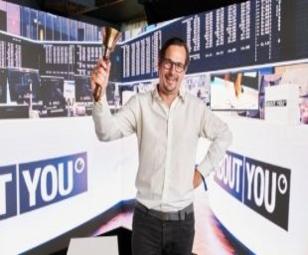 Marcel Esser mit einer Börsenglocke in der Hand vor einer LED-Wand beim ABOUT YOU Börsengang